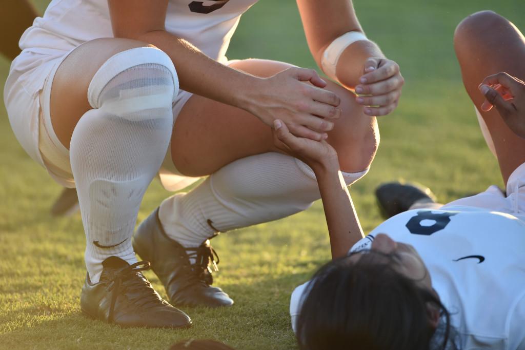 Friday women's soccer game, Fullerton College player comforting injured teammate.
